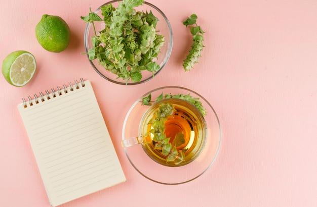 Tisane Aux Herbes, Limes, Cahier Dans Une Tasse En Verre Rose, Vue Du Dessus. Photo gratuit