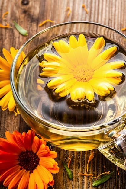 Tisane de calendula (marigold) dans une tasse en verre transparent avec des fleurs séchées sur fond rural en bois. Photo Premium