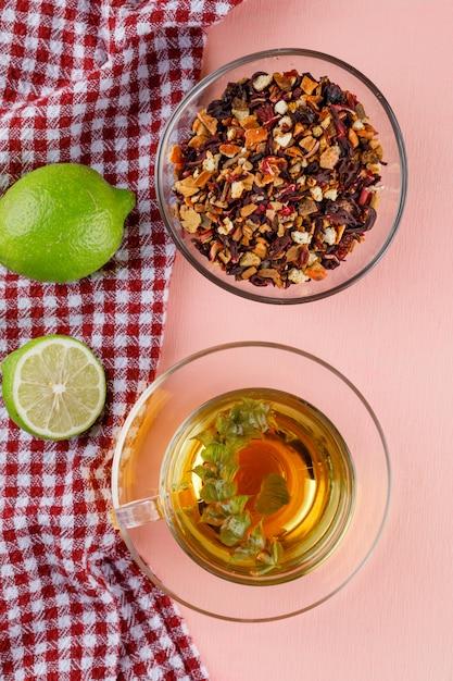 Tisane Dans Une Tasse En Verre Avec Limes, Herbes Séchées à Plat Sur Rose Et Torchon Photo gratuit