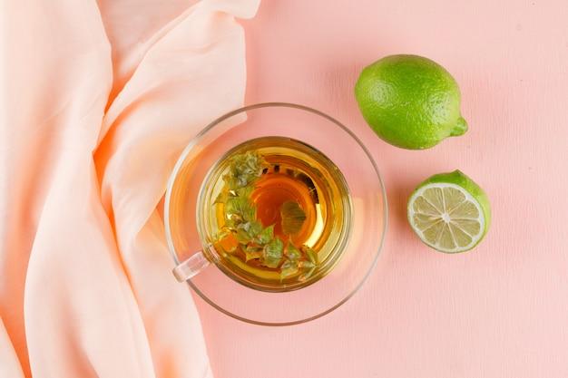 Tisane Dans Une Tasse En Verre Avec Des Limes à Plat Sur Rose Et Textile Photo gratuit