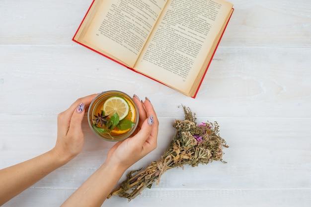 Une Tisane Avec Des Livres Et Des Fleurs Sur Une Surface Blanche Photo gratuit