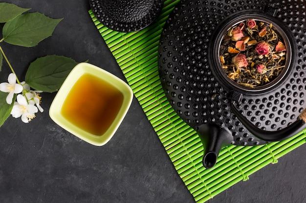 Tisane avec son ingrédient séché sur un napperon vert Photo gratuit