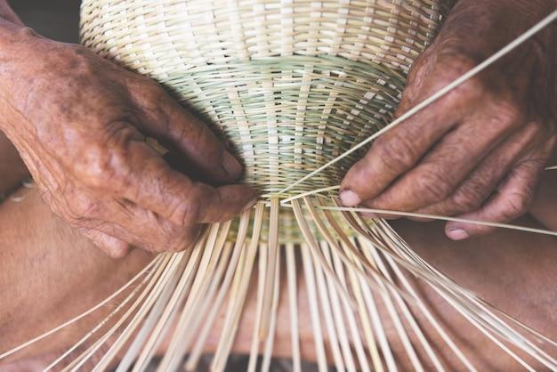 Tissage de paniers en bambou en bois, vieux homme âgé travaillant à la main avec un panier pour des produits naturels en asie Photo Premium