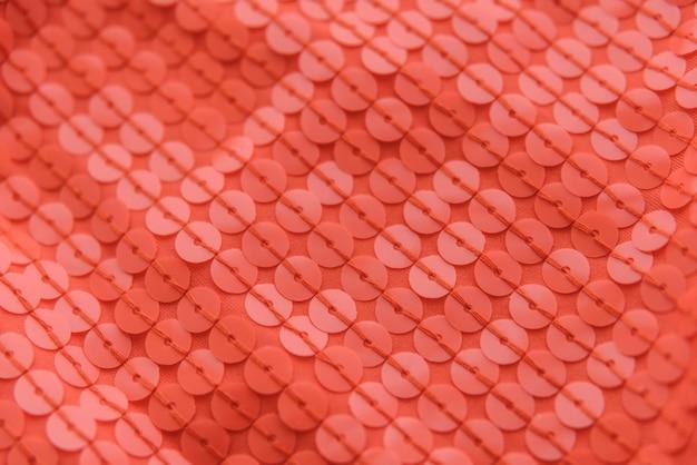 Tissu brillant corail avec des paillettes, abstrait. Photo Premium