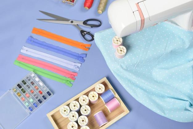 Le tissu à coudre à plat contient les tissus, les ciseaux, la fermeture à glissière, les aiguilles et les rouleaux de fil. Photo Premium