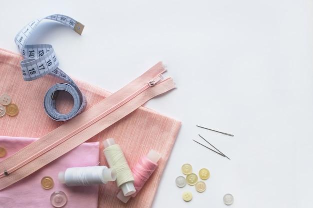 Tissu rose, fils à coudre, fermeture à glissière, aiguille, boutons et centimètre à coudre. vue de dessus, flatlay Photo Premium