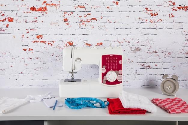 Tissu et ruban à mesurer près de la machine à coudre Photo gratuit