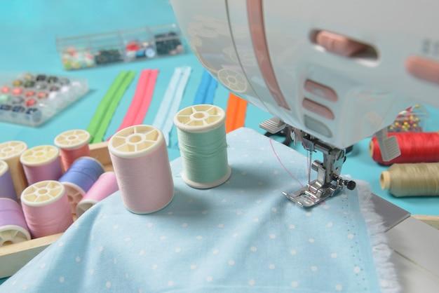 Tissus sur la machine à coudre parmi les ciseaux, les boutons de chemise, la fermeture à glissière, les broches et les rouleaux de fil. Photo Premium