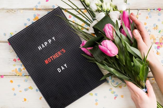 Titre de fête des mères heureux à bord avec une personne tenant un bouquet Photo gratuit