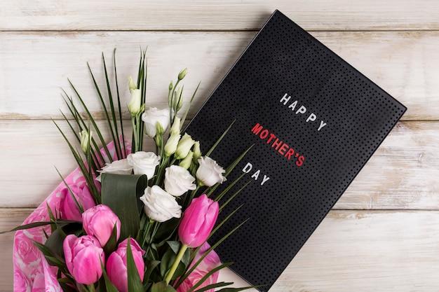 Titre de fête des mères heureux à bord près de bouquet de fleurs Photo gratuit