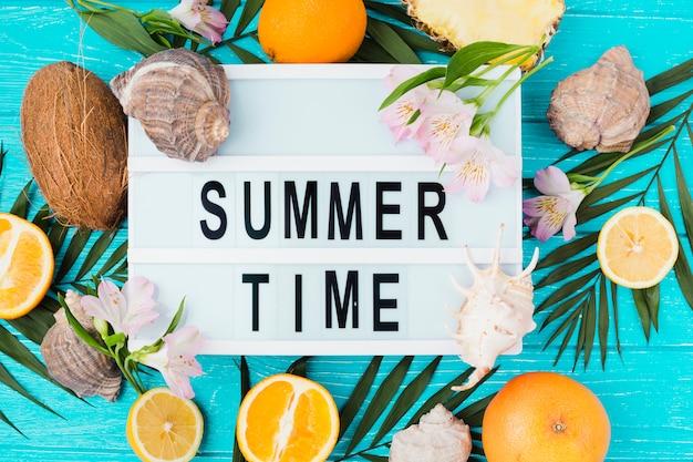 Titre de l'heure d'été sur la table parmi les feuilles des plantes près des fruits avec des fleurs Photo gratuit