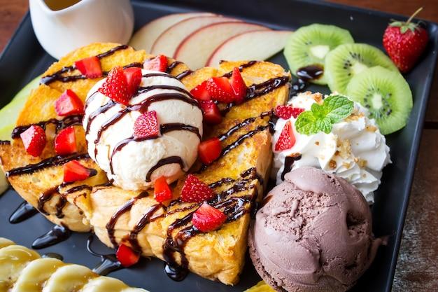 Toast au miel. dessert sucré servi avec variété de fruits et de glace. Photo Premium