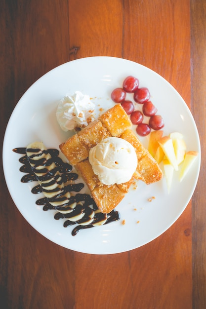 Toast au miel avec glace à la vanille, crème fouettée et sirop au chocolat. Photo Premium