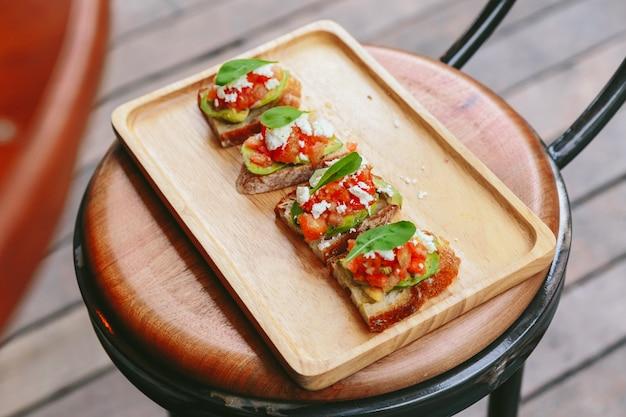 Toast à l'avocat avec tomates cerises et fromage féta, nappé de feuilles de roquette. servi sur une chaise en bois. Photo Premium