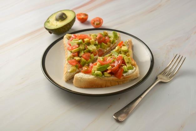 Toast avec du fromage à la crème, avocat et tomates cerises. la nourriture saine. Photo Premium