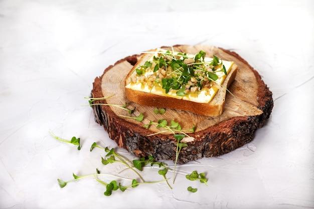 Toast Avec Du Fromage, Des Germes Et Des Noix Sur Un Support En Bois. Photo Premium