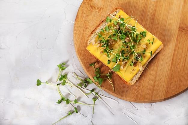 Toast Avec Du Fromage Et Des Pousses De Brocoli Sur Une Planche De Bois. Photo Premium