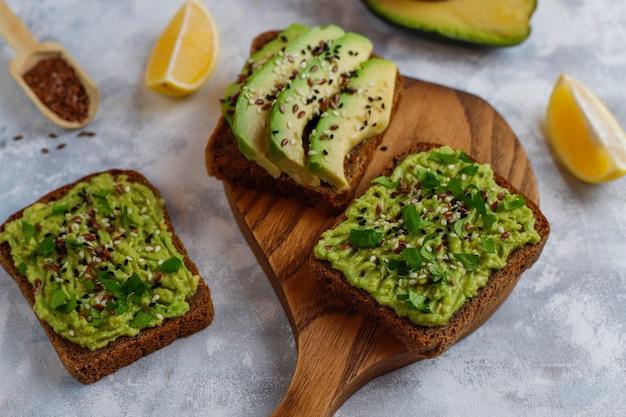Toast ouvert aux avocats, tranches d'avocat, citron, graines de lin, graines de sésame, tranches de pain noir, vue de dessus Photo gratuit