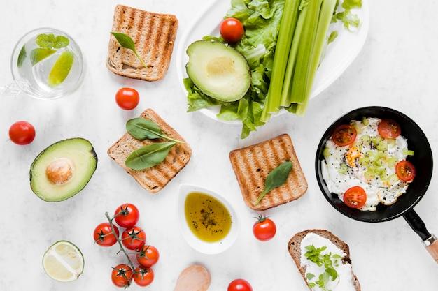 Toast plate poser avec des tomates avocat et des œufs Photo gratuit