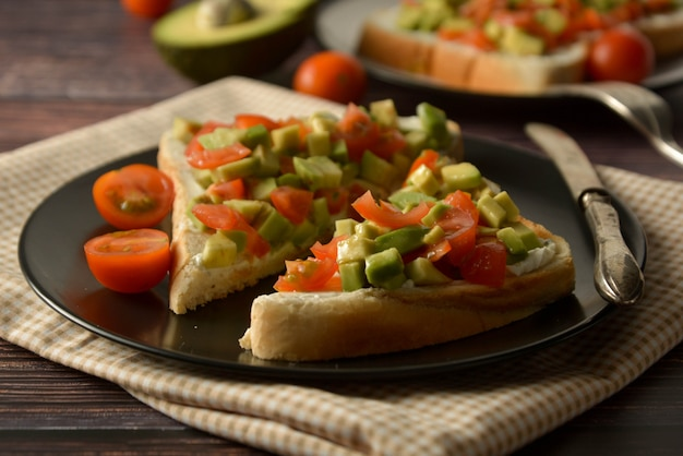Toast sain avec avocat, tomates cerises et fromage sur une assiette. table en bois. Photo Premium