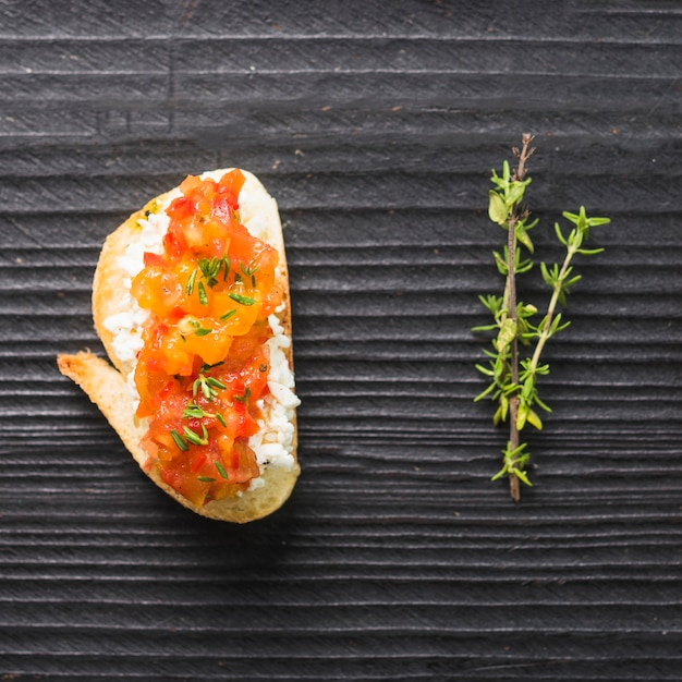 Toast sain avec du fromage et des tomates et du thym sur la toile de fond en bois Photo gratuit