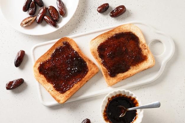 Toasts Croustillants Frais Avec De La Confiture De Dattes Sans Sucre Sur Tableau Blanc Photo Premium