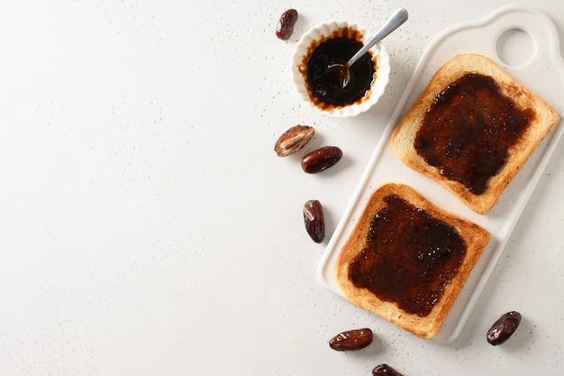 Toasts Frais Avec De La Confiture De Dattes Sans Sucre Sur Tableau Blanc Photo Premium