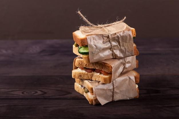 Des Toasts Frais Avec Du Saumon, Du Fromage à La Crème Et Des Légumes Se Trouvent Dans Une Pile, Enveloppés Dans Du Papier Kraft. Photo Premium