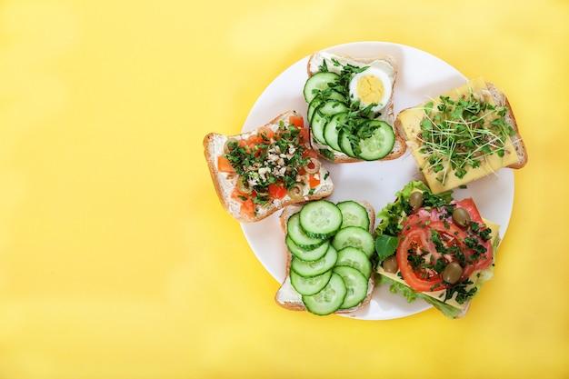 Toasts, Sandwichs Aux Concombres, Tomates, œufs, Pousses, Herbes Et Noix Sur Une Assiette Sur Un Jaune Photo Premium