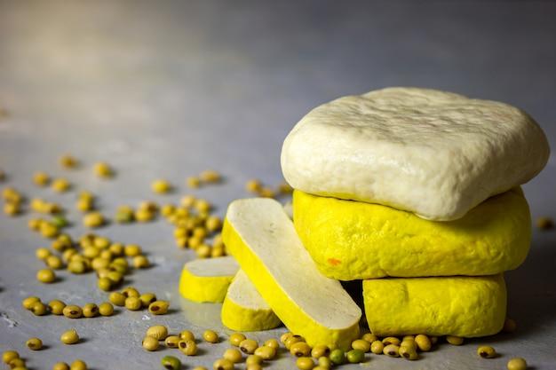 Tofu empilant sur la table et graines de soja dispersées sur la table. Photo Premium