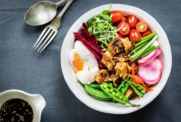 Tofu teriyaki avec un œuf à la coque, betterave rouge, petits pois et salade de riz Photo Premium