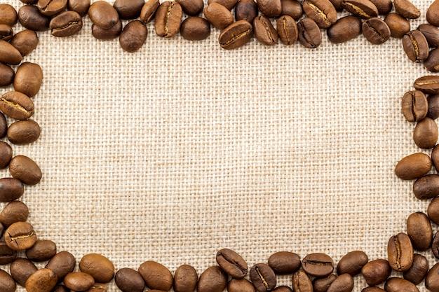 Toile de jute toile de sac et grains de café placés autour Photo Premium