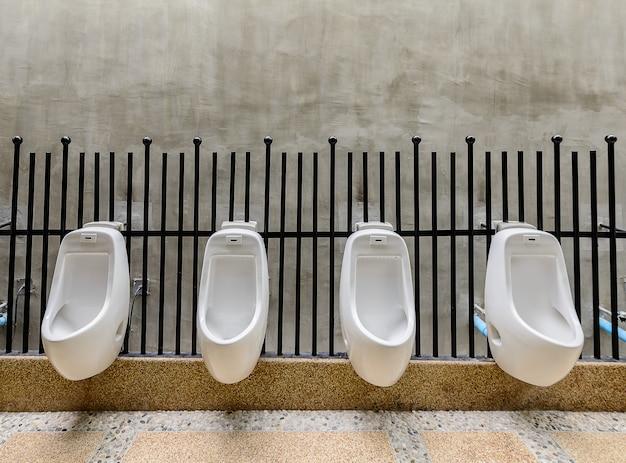 Toilettes publiques - urinoir avec toilettes confort pour hommes, urinoirs blancs dans des toilettes publiques Photo Premium