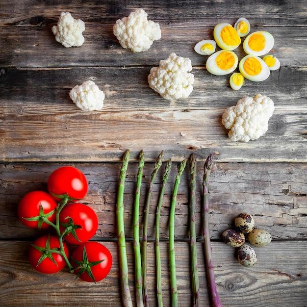 Tomates Aux Asperges, Oeufs, Chou-fleur Vue De Dessus Sur Un Fond En Bois Foncé Photo gratuit