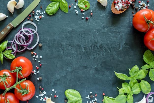 Tomates basilic ail et épices sur une table en pierre. le concept de la cuisine. vue de dessus avec un espace pour le texte Photo Premium