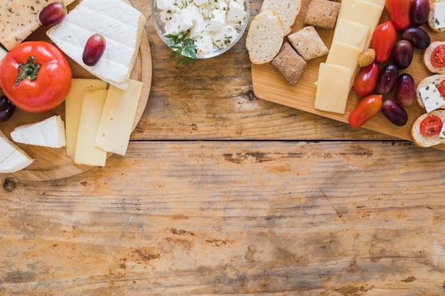 Tomates; blocs de fromage et raisins sur un bureau en bois Photo gratuit