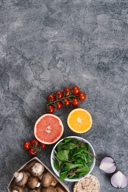 Tomates Cerises; Agrumes Coupés En Deux; épinard; Champignons; Gâteau D'oignons Et De Riz Soufflé Sur Fond De Béton Photo gratuit
