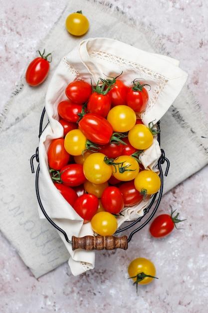 Tomates Cerises De Différentes Couleurs, Tomates Cerises Jaunes Et Rouges Dans Un Panier Sur Fond Clair Photo gratuit