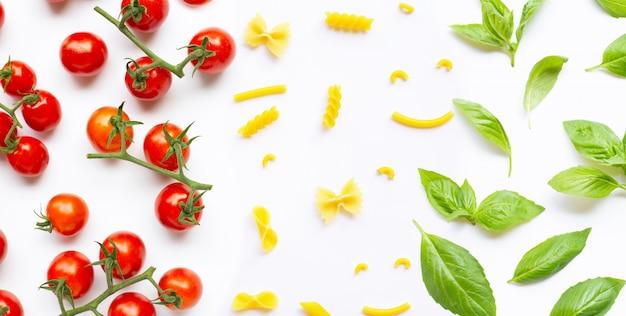 Tomates cerises avec différents types de pâtes et feuilles de basilic. concept de cuisine italienne Photo Premium