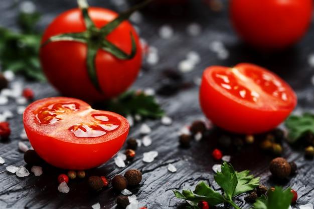 Tomates cerises fraîches en tranches avec épices gros sel et fines herbes Photo Premium