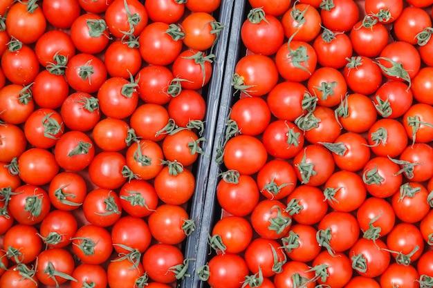 Des tomates cerises mûres fraîches et fraîches agrandi avec des tiges attendent d'être distribuées dans une boîte sur le marché de producteurs. Photo Premium