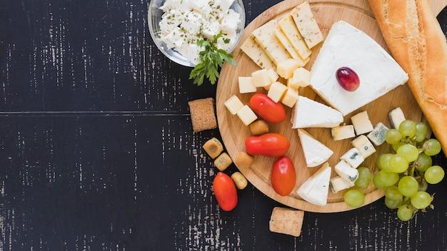 Tomates cerises, raisins, blocs de fromage et baguette sur une planche à découper ronde sur le fond texturé Photo gratuit