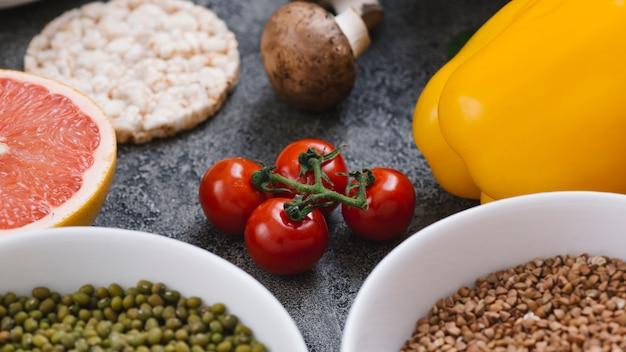 Tomates cerises rouges; champignon; gâteau de riz soufflé; pamplemousse; poivron; haricots mungo et graines de fenugrec Photo gratuit