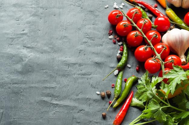 Tomates chili, ail et autres épices sur fond noir Photo Premium