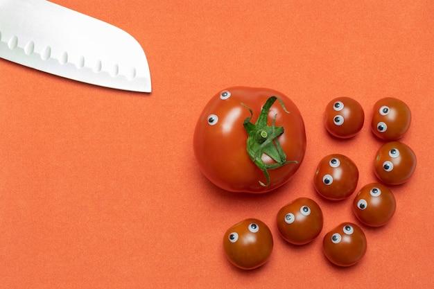 Tomates et couteau avec les yeux, concept de cuisine drôle, espace copie Photo Premium