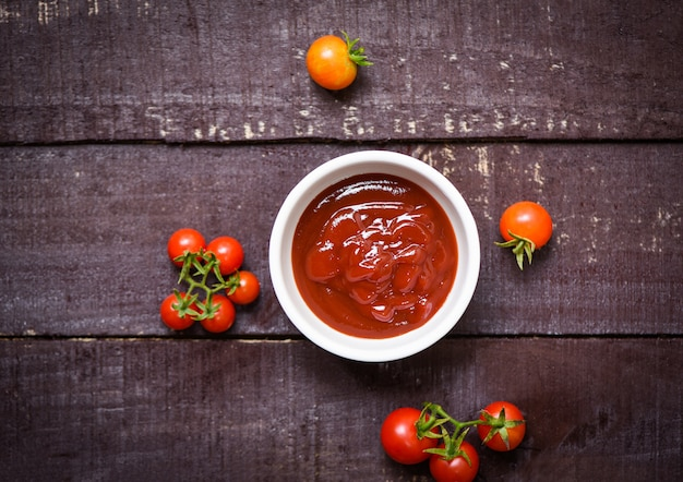 Tomates fraîches biologiques et ketchup dans une tasse de sauce tomate sur bois sombre - vue de dessus Photo Premium