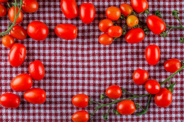 Tomates Fraîches à Plat Sur Un Chiffon De Pique-nique Photo gratuit