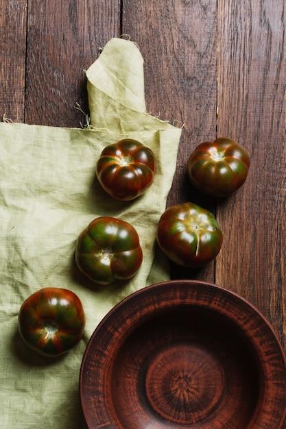 Tomates fraîches savoureuses sur fond en bois et tissu Photo gratuit