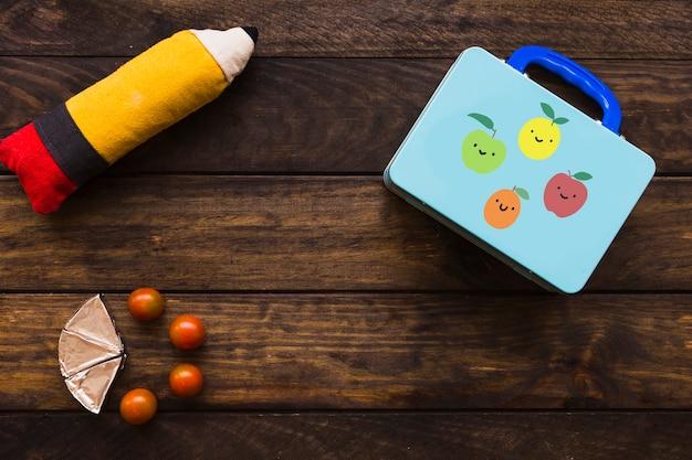 Tomates et fromage fondu près de la boîte à lunch et de l'étui à crayons Photo gratuit