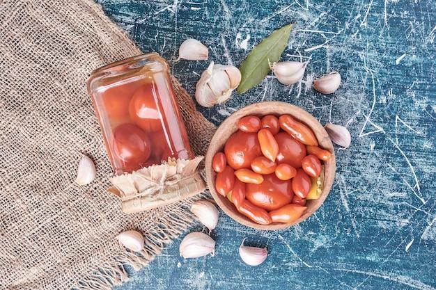 Tomates Marinées Dans Un Bocal En Verre Et Bol Avec De L'ail Sur Bleu. Photo gratuit